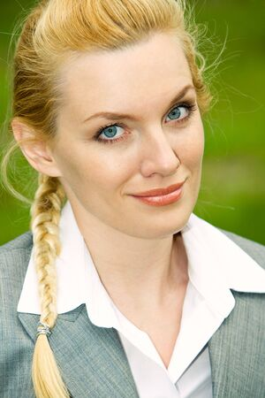 Face of smiling businesswoman looking at camera on green background photo