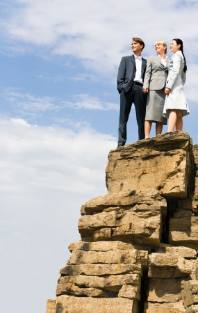 woman on top: Team of successful businesspeople stand together on the mountain