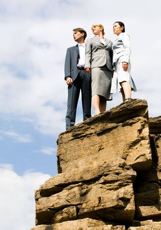 Portrait of business group standing on the mount peak and looking into the distance on the background of sky