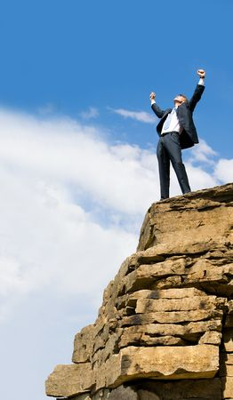 mountain top: View of successful businessman raising his hands