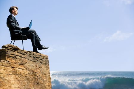 human height: Image of confident business man sitting on the top of rock with laptop and looking at sea below