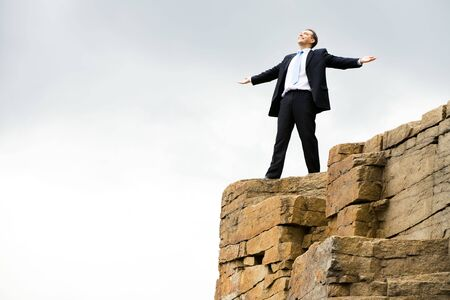 Happy businessman stands on the mountain and enjoys fresh wind  photo