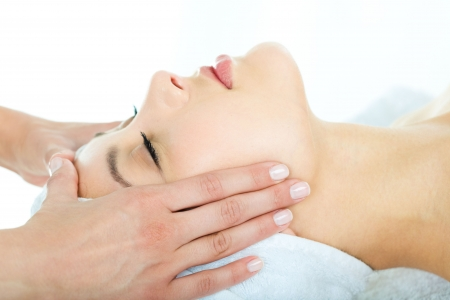 Photo of masseuse's hands doing relaxing massage on young woman's face Stock Photo - 3210284