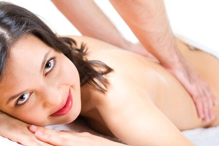Young woman looks at camera while masseuse makes massage to her Stock Photo - 3210304