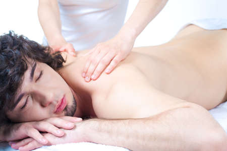 Portrait of young man with closed eyes and getting a relax massage photo