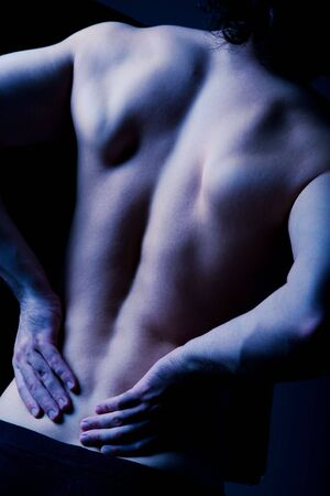 aching muscles: Dark image of human back pain with hands on it