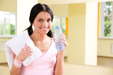 Portrait of sporty girl holding bottle with water in hand in the gym photo