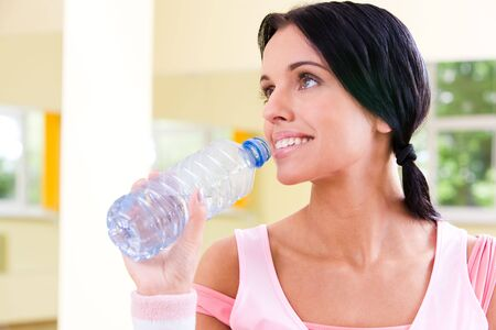 Close-up of pretty girl holding bottle of water by her mouth in the gymnasium photo
