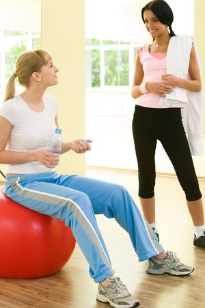 Image of two girls talking and looking at each other in the gym  photo