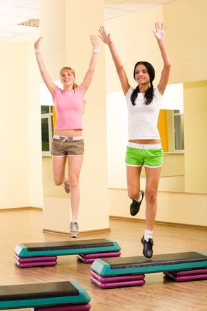 Image of cheerful young girls jumping up in the sports club photo