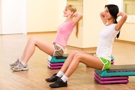 Two girls sitting in the gymnasium and practicing physical exercises photo