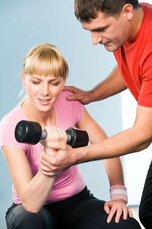Image of experienced instructor helping young lady lift barbell in the gym Stock Photo - 3210310