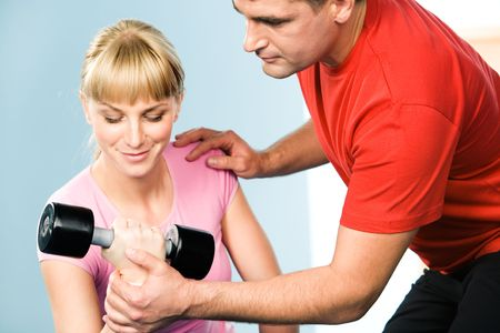 Image of pretty girl exercising with barbell in hand while the trainer assisting her  photo