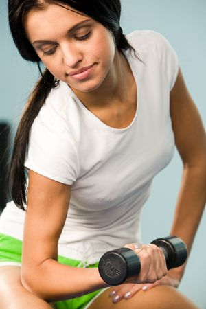 tanktop: Close-up of young woman sitting with barbell in hand and lifting it