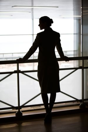 focus on foreground: Silhouette of business lady's back standing on the balcony and touching its railing Stock Photo