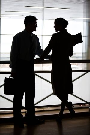 banisters: Silhouettes of two businesspeople standing on the balcony and looking at each other smiling