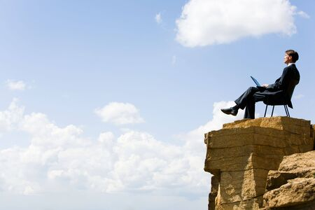 Image of pensive businessman sitting on the top of mountain with laptop and looking at the sky photo