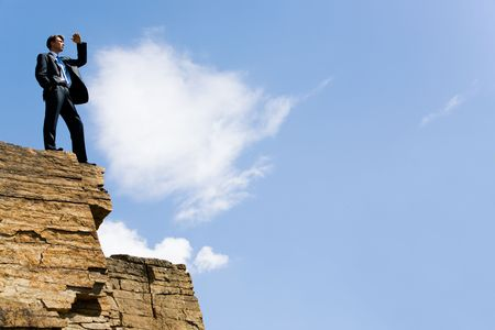 Image of elegant man standing on the cliff with his hand near forehead and looking forwards