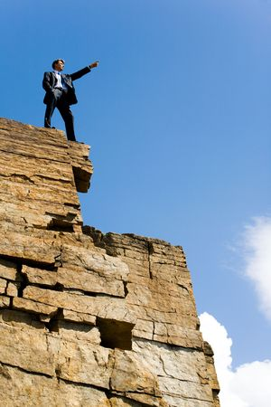 Image of confident man pointing to somewhere from the mountain top Stock Photo
