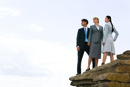 Image of confident business group standing on the top of mountain and looking aside  photo