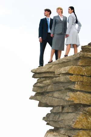 Vertical image of several business people standing on the rock and looking straight on the background of light sky photo