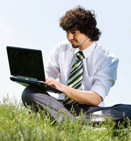 Portrait of young businessman doing computer work in the park  photo