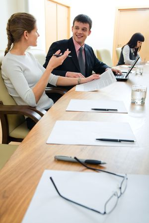 Portrait of business partners sitting in office and discussing their work on the background of working secretary photo