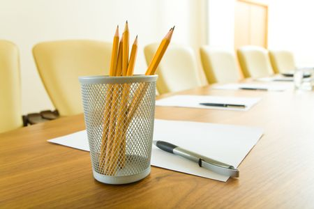 Photo of pencils in plastic glass, some pens and papers on the table in office  photo
