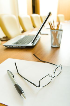 Close-up of glasses, pen and paper on the table on the background of laptop, pencils and armchairs photo