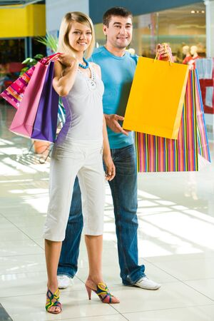 Portrait of smiling couple standing in shopping mall and looking aside Stock Photo - 3246310