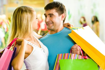 Close-up of man and woman with bags embracing each other in the department store Stock Photo - 3246304
