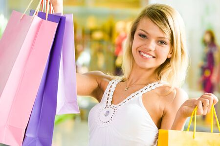 Portrait of blond girl holding shopping bags in hands and looking at camera with smile Stock Photo - 3246274