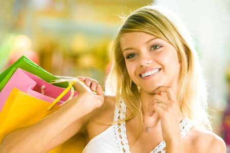 aside: Close-up of young woman touching her chin by hand and looking aside in the shopping mall Stock Photo