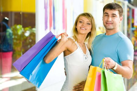 Portrait of man holding color shopping bags and embracing attractive girl   photo