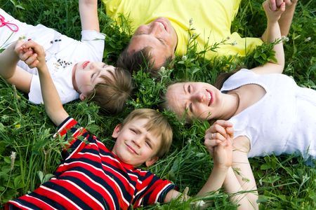 Portrait of family lying on the grass and holding their hands   photo