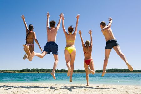 Image of backs of joyful friends jumping on the beach  photo