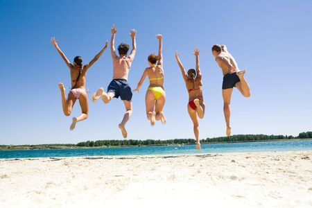 simultaneously: Photo of young people�s backs jumping on the sea shore simultaneously Stock Photo