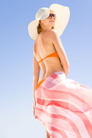 Portrait of young woman wearing hat, sunglasses, bikini and pareo standing on    background of clear sky photo