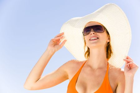 sunbathe: Close-up of pretty girl in hat and sunglasses on the background of blue sky