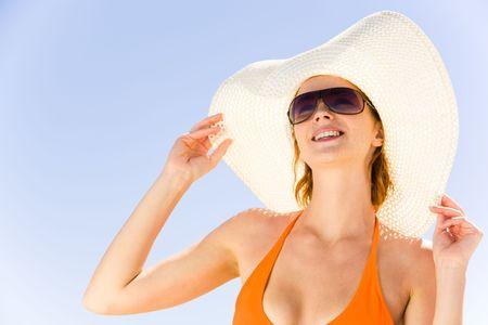 sunbath: Close-up van het meisje in de hoed en zonnebril op de achtergrond van een blauwe hemel