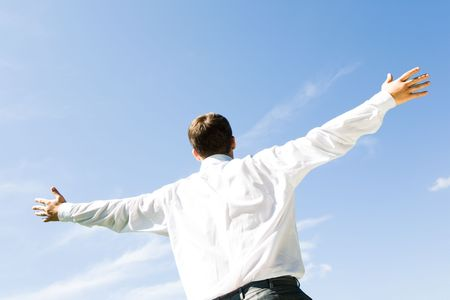 hands   free: Photo of businessman standing with his arms stretched on the background of blue sky