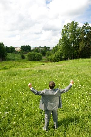 Image of joyful businessman standing on green meadow with his arms raised towards the sky photo