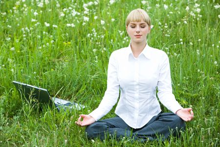 Portrait of meditating woman sitting on meadow in summer during break photo