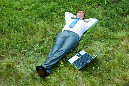 Image of businessman relaxing on the grass with laptop near by  photo