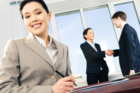Photo of Asian businesswoman looking at camera on the background of two partners shaking hands
