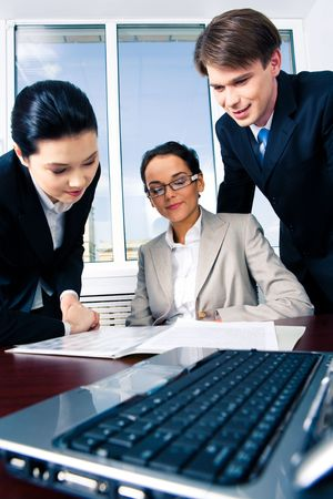 placed: Image of businesspeople discussing document placed on the table with laptop in front