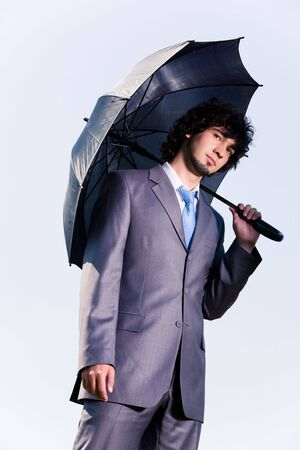 Portrait of serious businessman standing under his umbrella on blue background photo