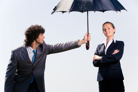 Photo of confident man protecting his coworker by umbrella from rain