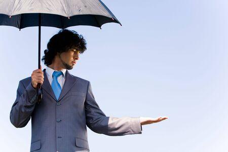 Portrait of confident businessman waiting a rain under the umbrella photo