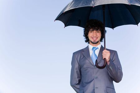 Image of successful businessman under his umbrella of background of sky photo